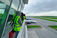 Spotting fans take  picture of planes on the territory of Pulkovo International airport in Saint-Petersburg, Russia Royalty Free Stock Image