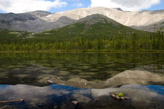 Spotty lake. A mountain lake with limpid water reflecting the hills behind it Stock Photography