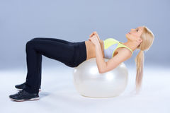 Spotty woman lying on fitness ball Royalty Free Stock Photography