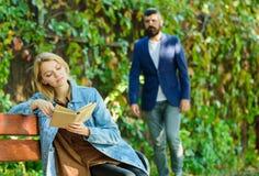 Spotykać each inny przy the first time Spotkanie mężczyzna i kobieta w parku kobieta w park czytającej książce Studencka edukacja fotografia stock