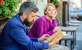 Spotykać ludzi z jednakowymi interesami Mężczyzna i kobieta siedzimy kawiarnia taras Dziewczyna ciekawił co on czyta literatura obrazy royalty free
