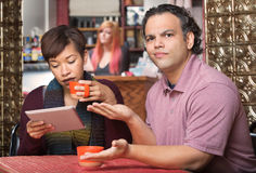 Spouse Reading Tablet and Annoying Husband. Annoyed spouse sitting with wife reading tablet computer Stock Images