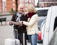 Spouses with baggage and map Royalty Free Stock Images