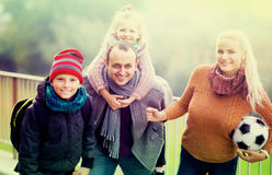 Spouses with children posing in autumn park Stock Photos