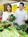 Spouses choosing veggies in store Royalty Free Stock Images