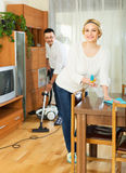 Spouses dusting and hoovering Royalty Free Stock Image
