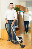 Spouses dusting and hoovering Stock Photos