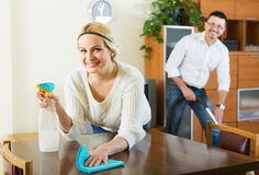 Spouses dusting and hoovering Royalty Free Stock Images