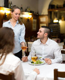 Spouses eating in a restaurant. Spouses eating out in a rural restaurant while young waitress is bringing them the food that they had ordered Stock Photography