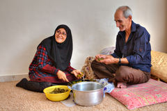 Spouses Muslims prepare national dishes, sitting on floor at hom Stock Photography