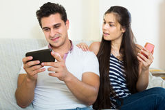 Spouses playing with smartphones Stock Image