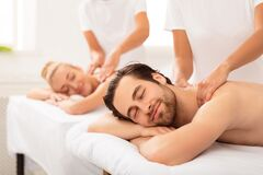 Spouses Receiving Neck And Back Massage Lying At Spa