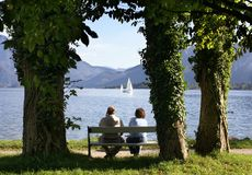 Spouses on rest. Lake in mountains, a married couple on a bench Royalty Free Stock Image