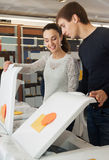 Spouses selecting new clothes washer. Happy spouses selecting new clothes washer in supermarket royalty free stock photo