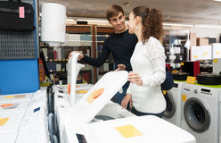 Spouses selecting new clothes washer. Happy spouses selecting new clothes washer in supermarket and smiling Stock Photography