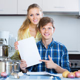 Spouses signing documents and smiling at kitchen Stock Photography