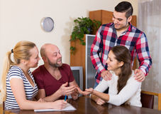 Spouses sitting with documents and asking friends for advice Royalty Free Stock Image