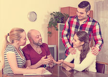 Spouses sitting with documents and asking friends for advice. Young american spouses sitting with documents and asking friends for advice Royalty Free Stock Photography