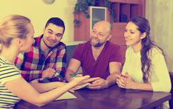 Spouses sitting with documents and asking friends for advice Royalty Free Stock Photography