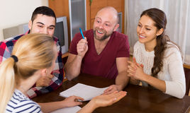 Spouses sitting with documents and asking friends for advice. Young russian spouses sitting with documents and asking friends for advice Royalty Free Stock Photography