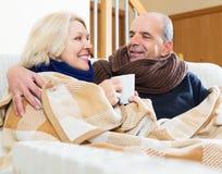 Spouses under blanket drinking tea Stock Photo