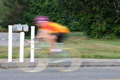 Spped. Man riding a bike past mail boxes stock photography
