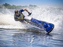 Spped on  jet ski. Man on jet ski turns with much splashes Royalty Free Stock Photography