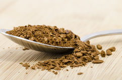 Sppon full of instant coffee. A spoonful of instant coffe on a wooden background/foreground Royalty Free Stock Photography