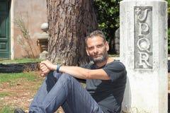Spqr man. Man sitting by Rome symbol SPQR Senatus Populusque Romanus Stock Photos