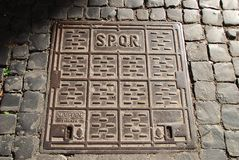SPQR manhole cover. Manhole cover with S.P.Q.R. and Firenze written on it, surrounded by cobblestones stock photo