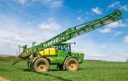 Sprüher John Deeres R4040i, der auf dem Weizengebiet sprüht Lizenzfreie Stockbilder