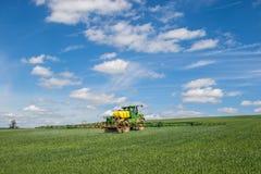 Sprüher John Deeres R4040i, der auf dem Weizengebiet sprüht Lizenzfreie Stockfotos