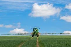 Sprüher John Deeres R4040i, der auf dem Weizengebiet sprüht Lizenzfreie Stockfotografie
