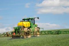 Sprüher John Deeres R4040i, der auf dem Weizengebiet sprüht Lizenzfreies Stockbild
