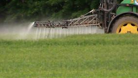 Sprüherntefeld mit dem Traktor und Sprüher, bewirtschaftend, ernten stock footage