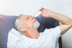 Sprühtropfen des älteren Mannes seiner Nase lizenzfreie stockfotos
