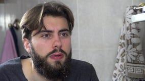 Sprühwasser des jungen Mannes auf seinem Gesicht nachdem dem Rasieren, Spritzwasser auf seinem Gesicht Mann, der sein Gesicht mit stock footage