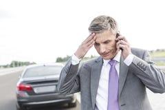 Sprężający biznesmen opowiada na telefonie komórkowym przeciw awaria samochodowi zdjęcie royalty free
