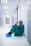 Sprężający męski chirurga obsiadanie w korytarzu Obrazy Royalty Free