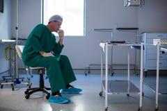 Sprężający męski chirurga obsiadanie w oddziale Obraz Stock