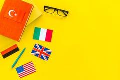 Sprachstudienkonzept Lehrbücher oder Wörterbücher der Fremdsprache nahe Flaggen auf gelbem backgrond Draufsicht-Kopienraum stockfotografie