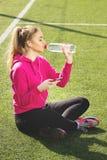 Spragniona młoda piękna blondynka włosy sprawności fizycznej dziewczyny woda pitna na stadium Lato sporta aktywność Zielona stadi obrazy stock