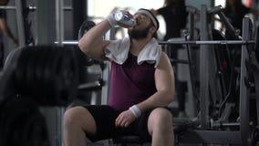 Spragniona szczęśliwa mężczyzna woda pitna po znojnego szkolenia, ciężar straty trening zbiory