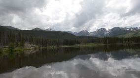 Sprague Lake Colorado Rocky Mountain National Park. Dramatic sky over trees and Continental Divide in Rockies Colorado stock video footage