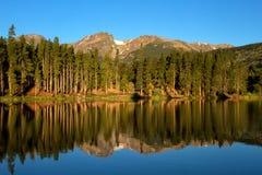 Sprague Lake in Rocky mountain National Park. Hallett Peak reflecting in Sprague Lake at Rocky Mountain National Park in Colorado. The tall pine trees reflecting stock photography