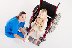 Sprain. Overhead shot of nurse bandaging a little girls sprain foot while she is sitting in wheelchair royalty free stock image