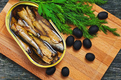 Sprat, greens and olives on a wooden background Royalty Free Stock Images