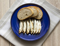 Sprats. Smoked sprats with bread on kitchen table Stock Image