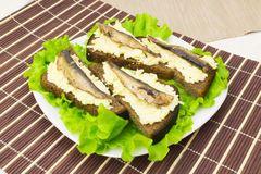 Sprats on bread with cheese and garlic Royalty Free Stock Photo