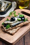 Sprats, herbs and olives on bread Stock Images